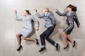 Young people in business suits lying on floor