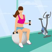Beautiful woman exercising with two dumbbell weights sitting on the fitness ball