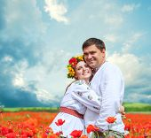 Happy Couple In National Ukrainian Dress On Poppies Field
