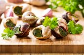 image of escargot  - escargots with parsley on a wooden table - JPG