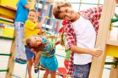 stock photo of adolescence  - Image of joyful friends having fun on playground outdoors - JPG