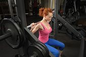 young red haired girl doing squats with barbell on smith machine