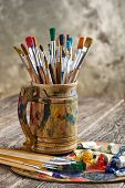 picture of bristle brush  - Paint brushes and oil paint laid on the table in the composition - JPG