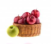 Red and green apples in a wicker baskets, isolated on white background.