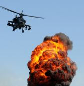 stock photo of attack helicopter  - Attack helicopter flying over fire and smoke - JPG