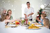 stock photo of christmas meal  - Composite image of Family enjoying Christmas meal at dining table against snow - JPG