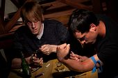 stock photo of opiate  - Two men with heroin cooking in a bent spoon - JPG