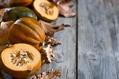 stock photo of fall decorations  - Decorative small pumpkins on fall leaves and wooden background. Selective focus. Copyspace background. ** Note: Shallow depth of field - JPG