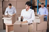 stock photo of warehouse  - Warehouse workers packing up boxes in a large warehouse - JPG
