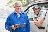 stock photo of loading dock  - Delivery driver smiling at camera with customer outside the warehouse - JPG