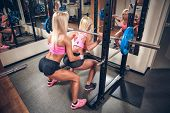 foto of squat  - Young sexy women in the gym doing squat with barbell - JPG