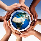 stock photo of peace-sign  - Conceptual peace and cultural diversity symbol of multiracial hands making a circle together around the world the Earth globe on blue sky background - JPG