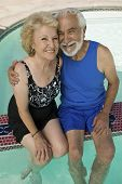 Senior Couple sitting on edge of swimming pool elevated view portrait.