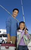 pic of road trip  - Father and daughter holding fishing poles outside RV - JPG