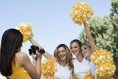 Female Cheerleader video taping fellow cheerleader friends