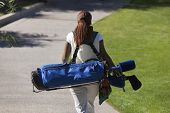 image of golf bag  - Woman carrying golf club bag rear view - JPG