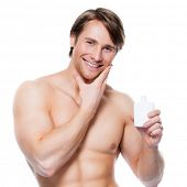 foto of body-lotion  - Young happy smiling man applying lotion on face  - JPG