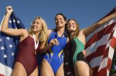 Three female swimmers celebrating victory (low angle view)