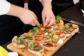 stock photo of pesto sauce  - Chef is making bruschettas with beefsteak and pesto sauce - JPG