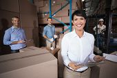 picture of warehouse  - Warehouse workers preparing a shipment in a large warehouse - JPG