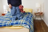 picture of stuffed animals  - Boy standing on bed holding stuffed animal - JPG