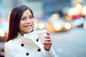 pic of cabs  - Young casual urban professional woman in New York City Manhattan drinking coffee walking in street wearing coat downtown with yellow taxi cabs in background - JPG