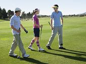 picture of young adult  - Three young caucasian golfers on course holding various golf clubs - JPG