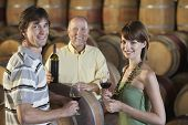 Three people wine-tasting beside wine casks portrait