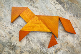 foto of tangram  - abstract picture of a horse built from seven tangram wooden pieces against slate rock background - JPG