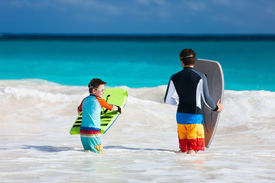 foto of boogie board  - Father and son running towards ocean with boogie boards having fun on beach vacation - JPG
