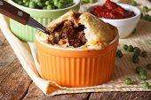 foto of green pea  - Australian meat pie in a pot on a background of green pea - JPG