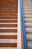 stock photo of escalator  - Full frame take of a staircase next to an escalator - JPG