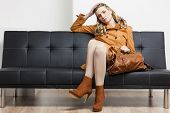 picture of leggins  - woman wearing brown coat with a handbag sitting on sofa - JPG
