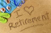 picture of retirement age  - Beach background with towel and flip flops and the words I Love Retirement written in sand - JPG