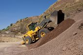 stock photo of bulldozers  - bulldozer in action in a big quarry - JPG