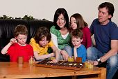 picture of boardgame  - Big family is playing a boardgame in the livingroom - JPG