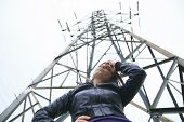 image of electricity pylon  - A woman at the bottom of a electricity pylon - JPG