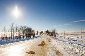 stock photo of slippery-roads  - winter slippery road disappearing into  horizon on a bright sunny sky - JPG