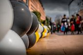 stock photo of pedestrians  - Colored balloons line the footpath of a main pedestrian thoroughfare. ** Note: Shallow depth of field - JPG