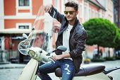 picture of vespa  - Handsome man riding a vintage scooter - JPG