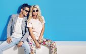 stock photo of blue  - Young fashionable couple on blue background - JPG