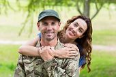 stock photo of reunited  - Handsome soldier reunited with partner on a sunny day - JPG