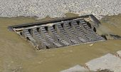 stock photo of manhole  - Melted water flows down through the manhole - JPG