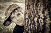 image of newsboy  - Young boy with newsboy cap sneaking behind a tree and playing detective - JPG