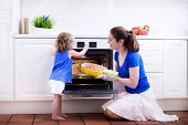 stock photo of helping others  - Mother and child bake a pie - JPG