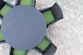 foto of paving  - Six seater outdoor patio set with comfortable green cushions and a round dining table on a brick paved open - JPG