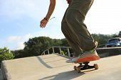 picture of skateboard  - skateboarder legs riding on skateboard skatepark ramp - JPG