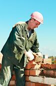 stock photo of trowel  - construction mason worker bricklayer making a brickwork with trowel and cement mortar - JPG