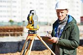 pic of theodolite  - Surveyor builder worker with theodolite transit equipment at construction site outdoors during surveying work - JPG