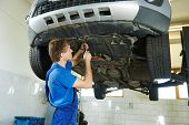pic of auto garage  - garage auto mechanic repairman assembling bottom car protection during car suspension repair of automobile maintenance at repair service station - JPG